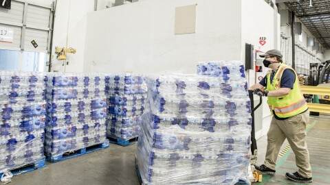 A man wearing a yellow safety vest and face mask maneuvers a pallet of water bottles in a warehouse setting.