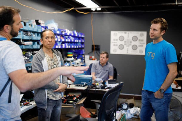 Jamie Siminoff, founder of Ring, in a blue t-shirt and jeans, talks to engineers in a lab at Ring headquarters in Santa Monica, CA.