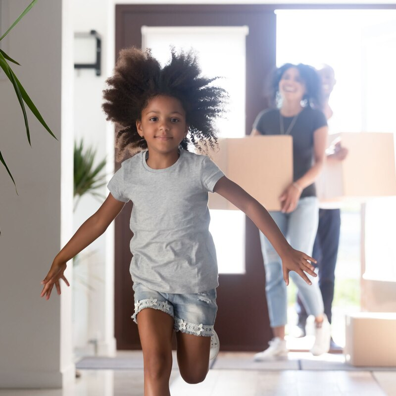 A little girl runs into a house.  Adults carrying moving boxes into the home are out of focus behind her.
