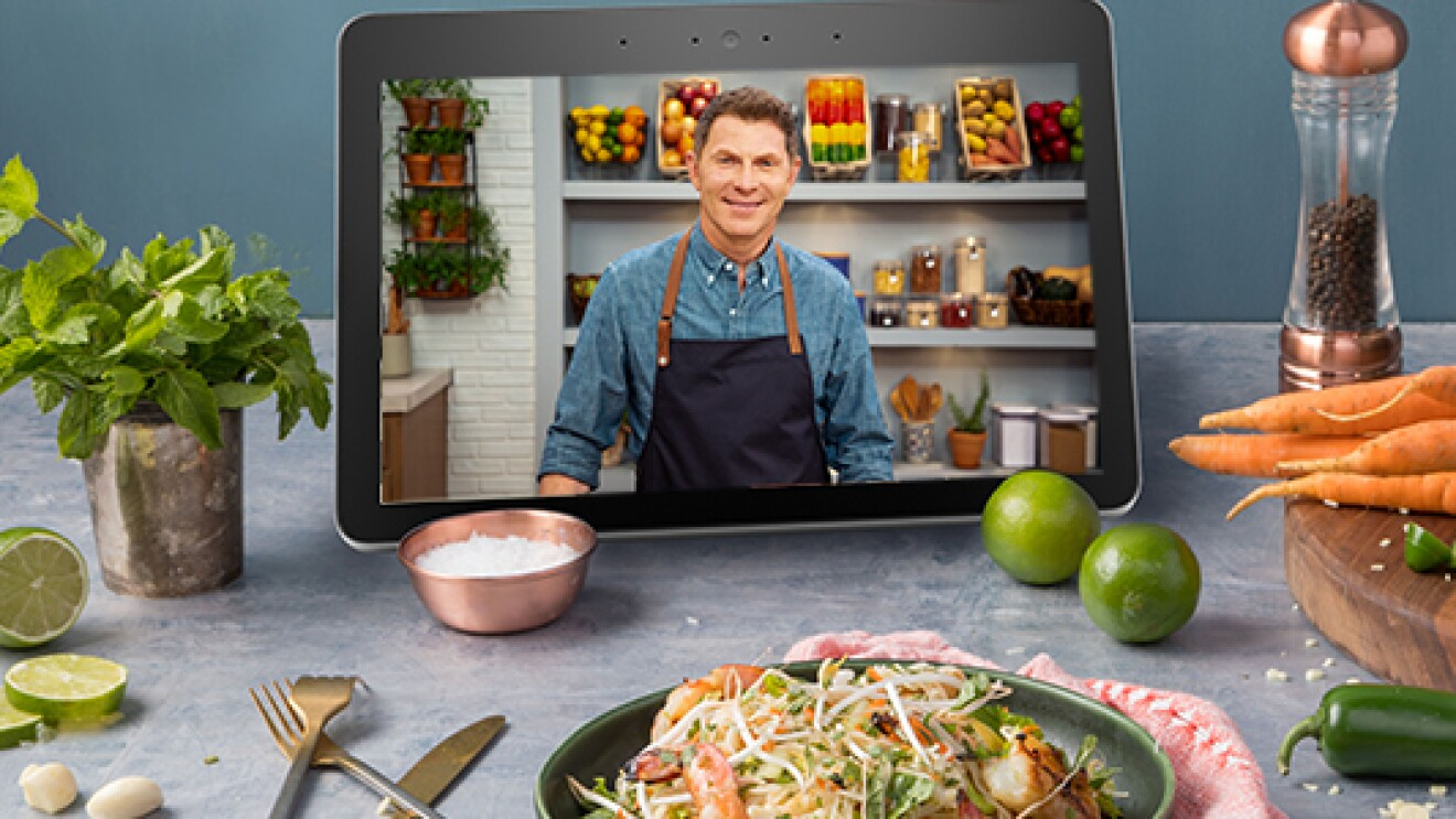 An image of an Echo Show device sitting on a kitchen counter top next to a plate of food. Bobby Flay's cooking class plays on the screen.