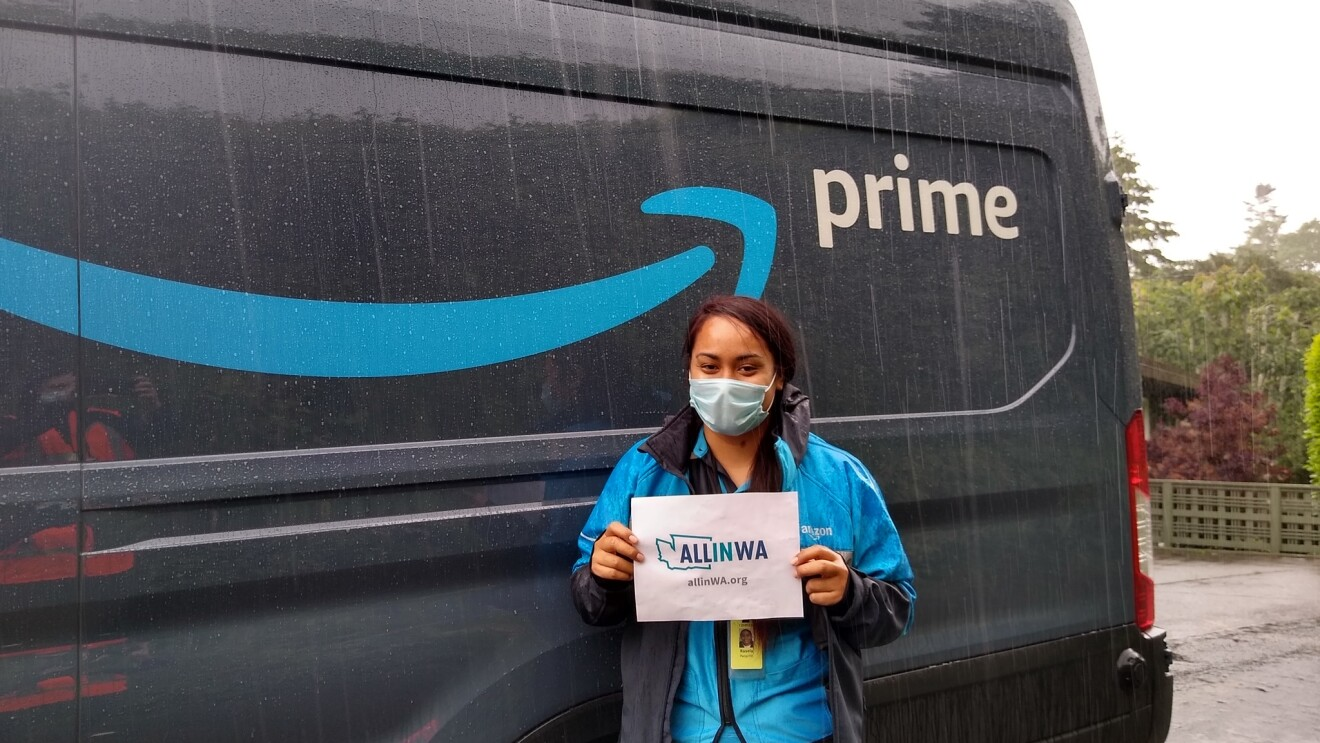 "Amazon associate holds a sign that says ""All in WA"""