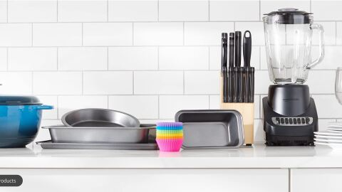 An assortment of kitchen supplies, dutch oven, baking pans, muffin liners, blender, and plates, on a kitchen countertop