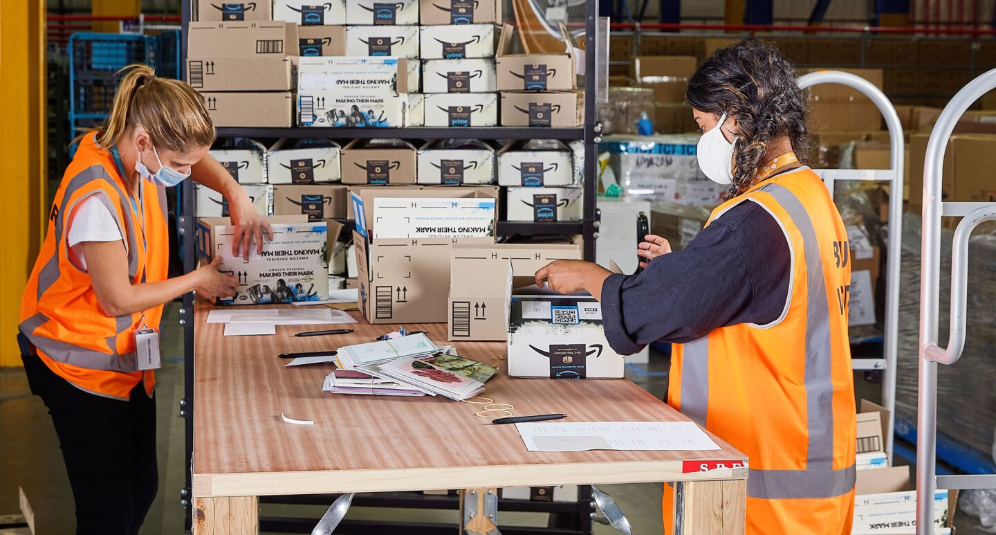 Two women wearing safety vests and face masks pack Amazon boxes on a table in support of disaster relief efforts.