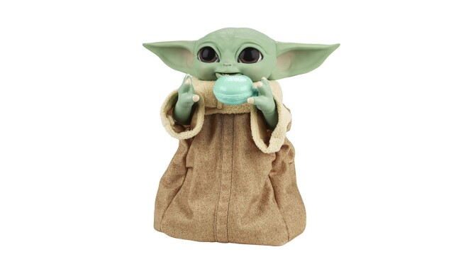 An image of the baby yoda from Star Wars The Mandalorian Galatic holding a tea cup and smiling.