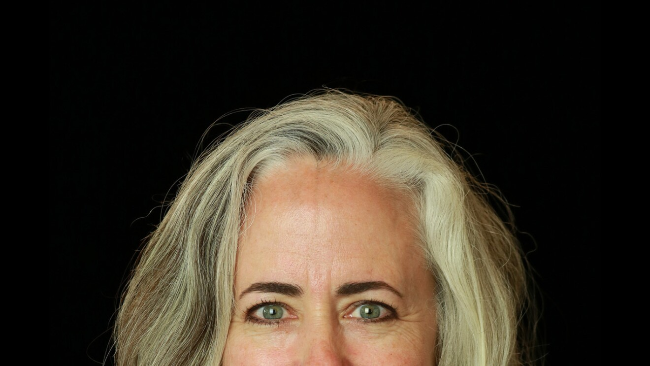 A woman with blonde hair smiles at the camera, she sits in front of a black background.