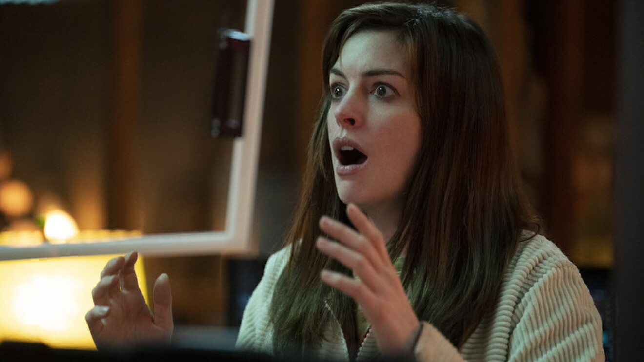 An image of Anne Hathaway looking shocked and surprised with her hands raised in front of her.