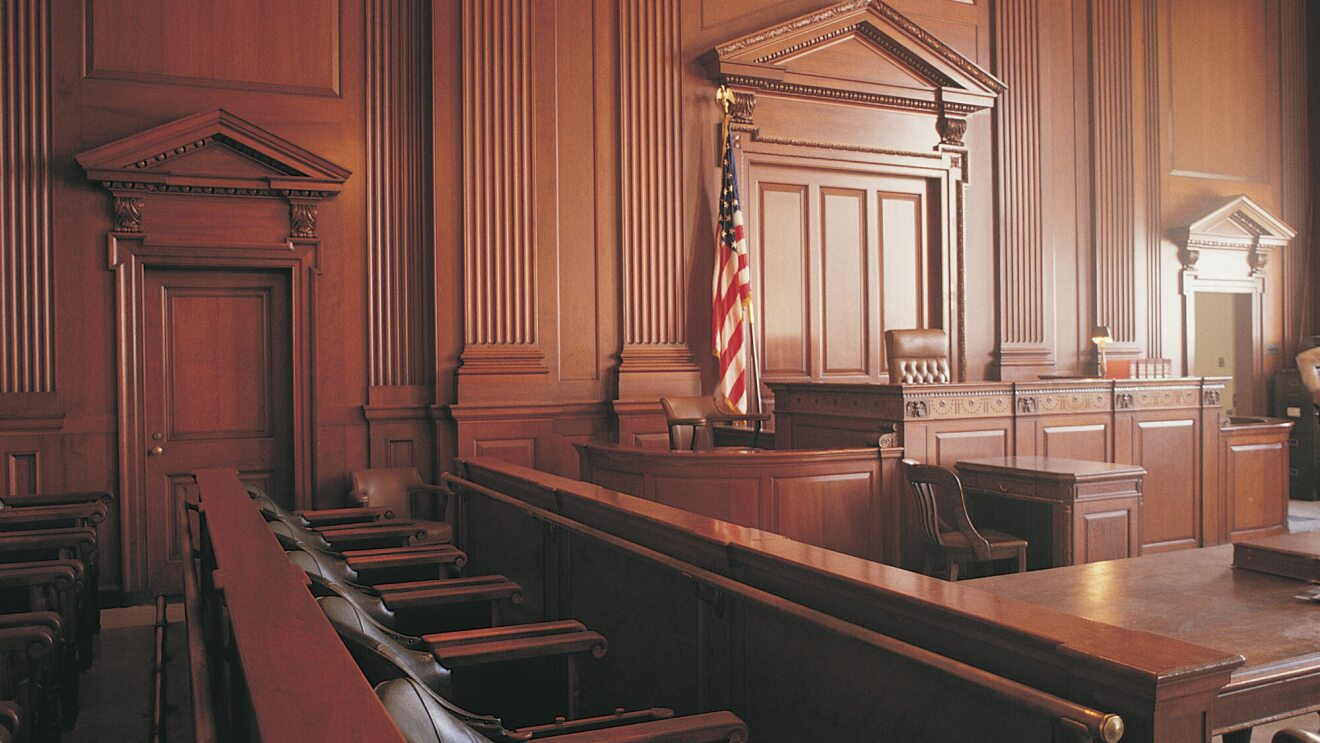 An unoccupied, architecturally striking, wood-paneled courtroom from inside the jury box, facing the Judge's bench.