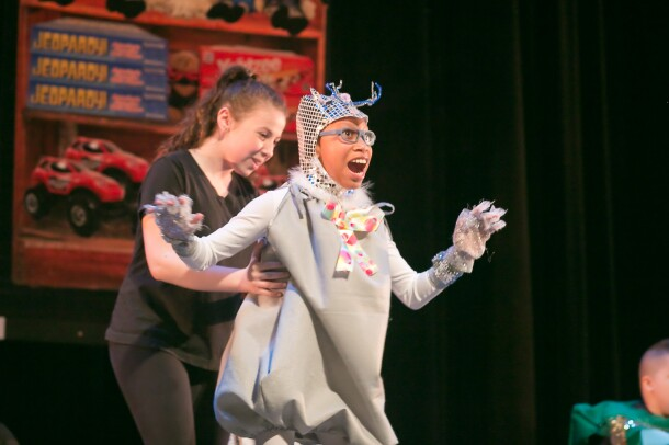 A costumed dancer performs with the support of a helper. Stage decorations in the background show toys and board games.