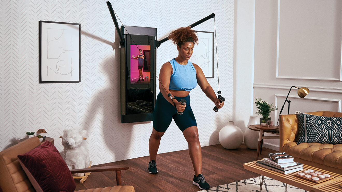 A woman exercises in her living room.