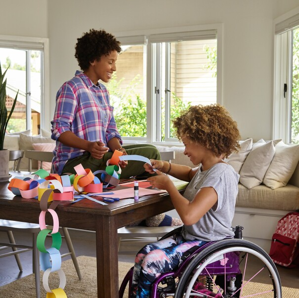 A mother sits on a dining room table, as she and her daughter laugh, while making a paper chain. Behind them, Amazon Echo is on a console table.