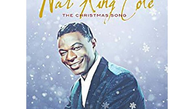 """Nat King Cole wears a suit, facing the camera with a smile. The background is a blue-gray and appears to fade from light to darker gray-purple. Snow falls around him, with snowflakes in front of him. Nat King Cole is scrawled across the top in gold, with """"The Christmas Song"""" in red, below."""