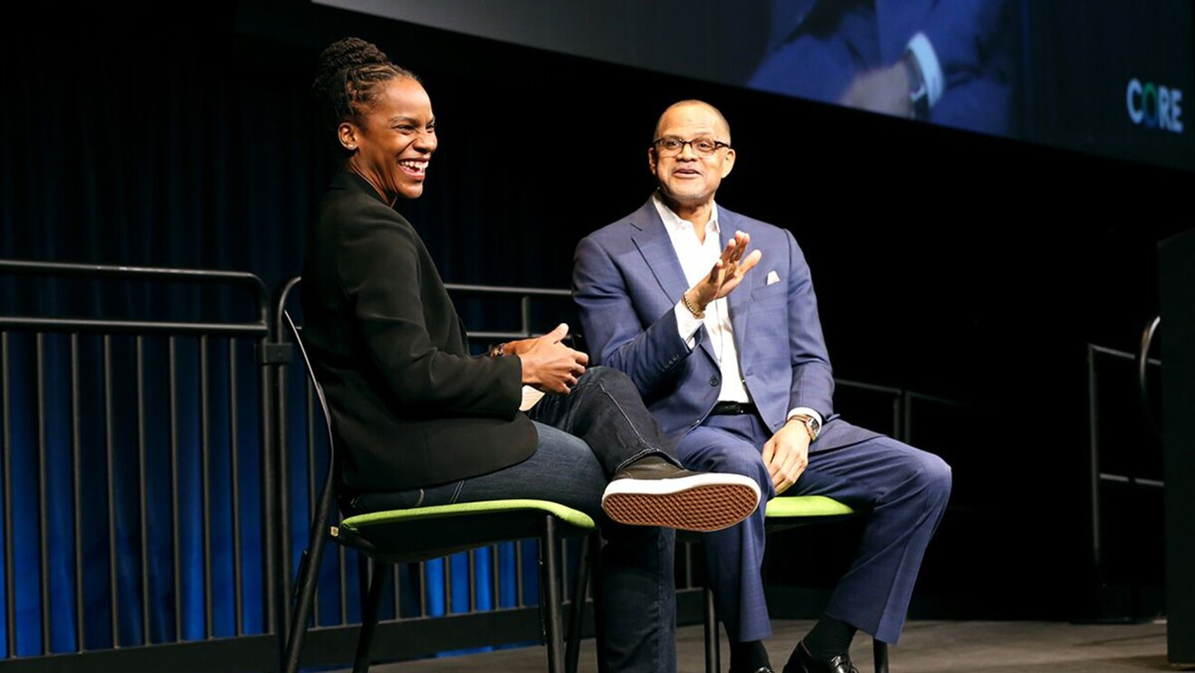 A woman in blue jeans and a black jacket smiles during a Q&A session onstage.