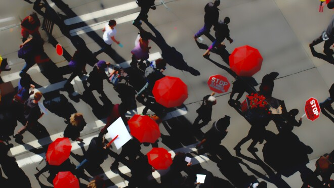 Protesters carrying red umbrellas and red signs that say STOP are photographed from above crossing an intersection. It is a photography piece of art.