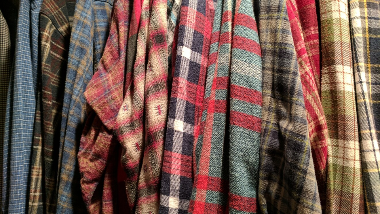 A row of flannel shirts, hanging in a closet