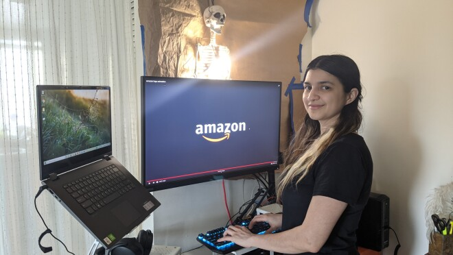 An image of an Amazon intern sitting at her computer at home, smiling for a photo with the Amazon logo on her screen in the background.