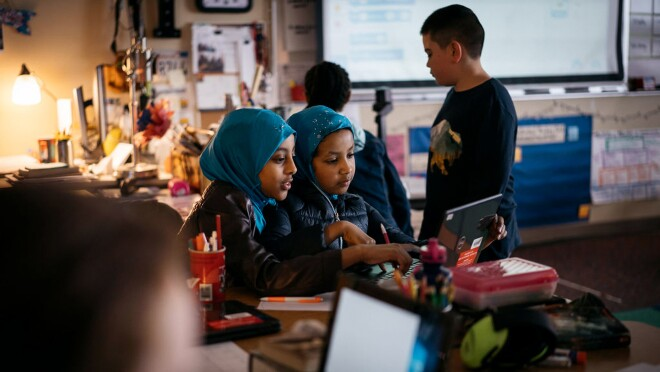 Two students in hijabs study coding at an Amazon-provided laptop