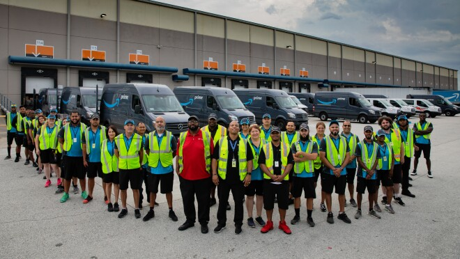 A group of employees stand in front of a fleet of Amazon Prime-branded cargo vans.