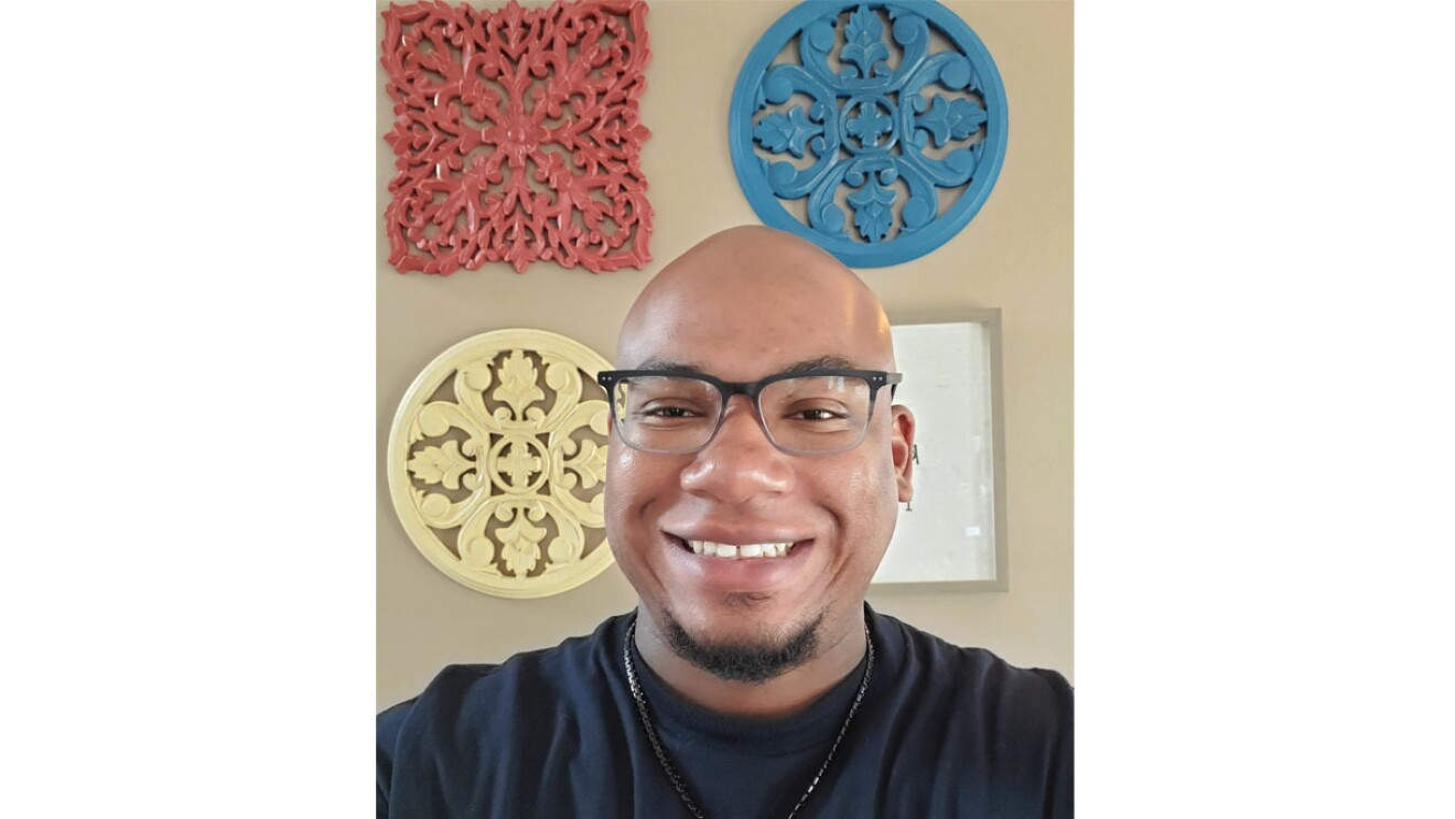 An image of a man wearing glasses and smiling for a photo at his home in front of a wall with colorful, circular decorations on it.