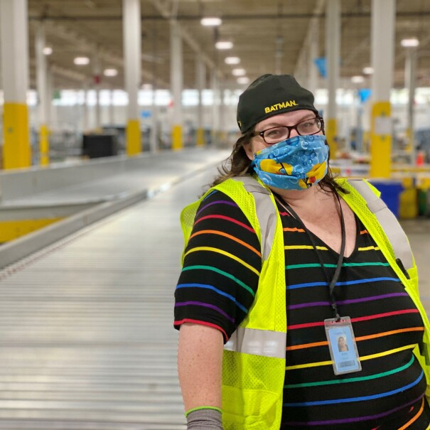 A woman wearing a rainbow-striped shirt, a colorful face mask, and a yellow safety vest stands in an Amazon fulfillment center, smiling at the camera from behind her mask.