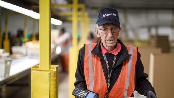 Amazon employee Rick Reefer. He is holding a scanner and a bin, and wearing a cap that says 'Mohegan Sun'.