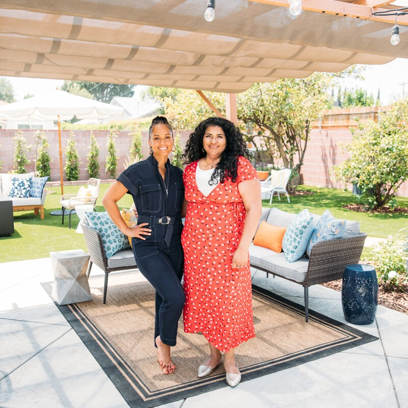 An image of Alicia Keys standing next to a woman in her newly remodeled backyard. Both women are smiling, and Alicia has her arms around the other woman and is looking at her.
