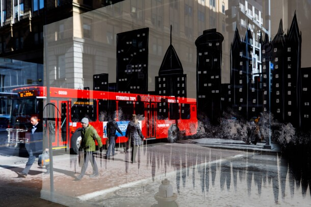 A street in Pittsburgh, PA is reflected in a glass window. There is a red bus and individuals on the street. It's winter and there is light snow on the ground.