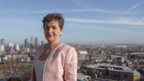 Christiana Figueres standing on a balcony overlooking a city skyline.