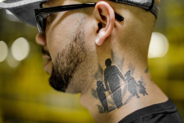 A man wearing glasses is pictured in profile from the shoulders up. He wears glasses and has a beard. A tattoo covers much of the left side of his neck. It shows an adult figure holding hands with three children. All the figures are in silhouette.