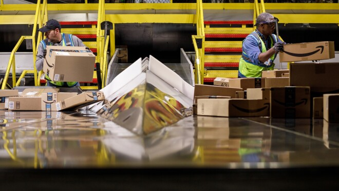 Two Amazon associates handle packages at an Amazon fulfillment center, PIT5, in Pittsburgh, PA