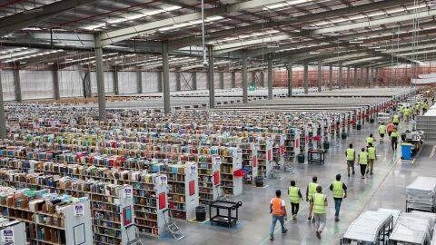 An image from the top of an Amazon fulfillment center. There are rows of shelves of products on the left of the photo and employees with their safety vests on walking alongside a walkway to the right of the photo.