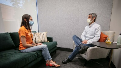 A man and a woman sit in a clinic setting wearing masks while speaking.