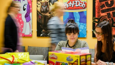 Two women in the foreground sit at a table surrounded by packaging. Other people pass by in the background. The wall has posters of My Little Pony, Play-Doh, and other Hasbro brands.