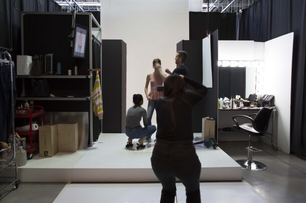 Two assistants, one male and one female, assist a model during an Amazon Fashion shoot. The photographer, who is silhouetted, is in the foreground.