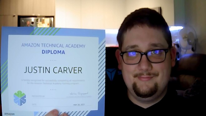 Justin Carver holds up his ATA diploma while he smiles for the camera. He wears a black shirt and black-framed eyeglasses.