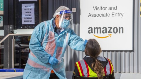An worker at Amazon's Sydney fulfilment centre is given a COVID-19 test at the new onsite testing station