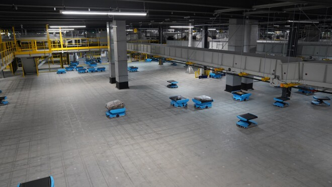 An image of small blue robots on the floor of the sortation center. They are carrying packages.