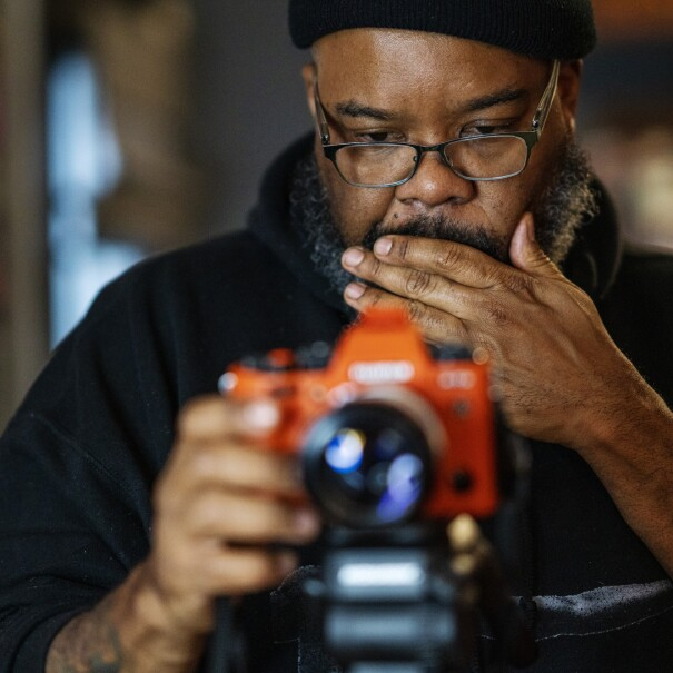 A man in glasses operates a camera mounted on a tripod.