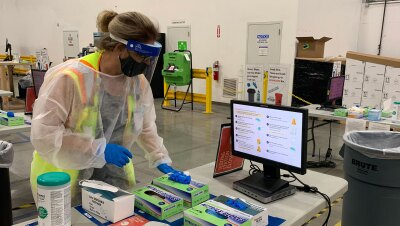 A woman in full COVID-19 personal protective wear and a safety vest stands next to a table that has COVID-19 testing supplies and a computer monitor.