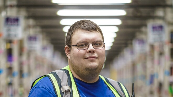 A man poses holding a laptop computer. He wears glasses, a blue T-shirt, and a yellow safety vest.