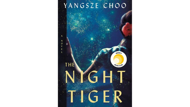 """Book cover for """"The Night Tiger"""" by Yangsze Choo, shows a woman leaning on a doorway, her arm bent as she leans, wearing a short-sleeved frock, with a flower in her tied-back hair. In front of her is a darkened blue landscape with flashes of light."""