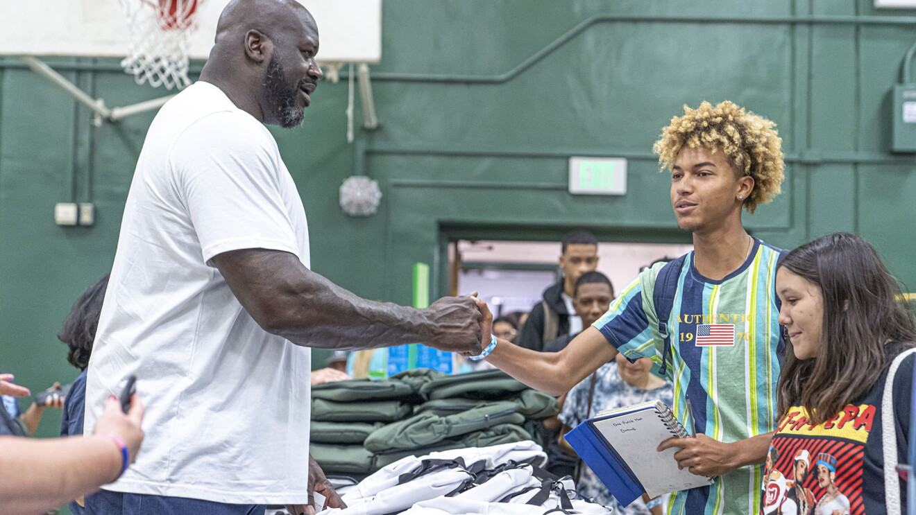 Shaquille O'Neal meets a young student at a school donation event