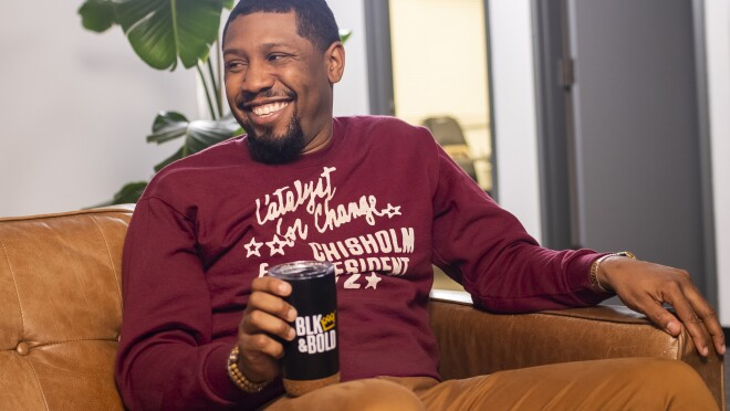 A smiling man sits on a couch and holds a coffee tumbler.