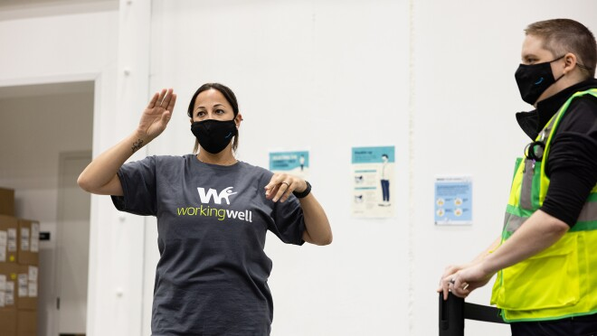 An image of Leila Brown wearing WorkingWell shirt and a mask with the Amazon logo on it as she speaks to employees in her fulfillment center.