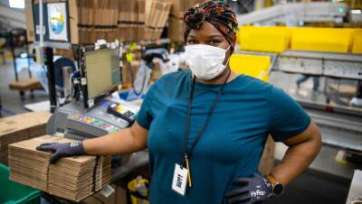 An Amazon associate working at a fulfillment center pack station poses for the camera while wearing a protective surgical mask.