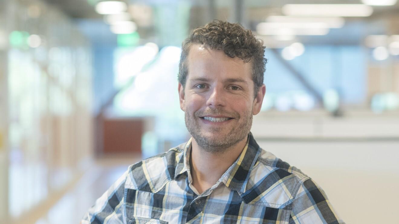 A man wearing a plaid shirt, smiling at the camera.