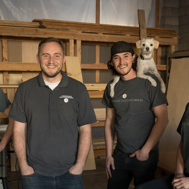 Three males, and a female stand in front of a wall of wood. One of the men has a dog perched on his shoulders. These four individuals are siblings who run a small business named Perida Rice, which sells on Amazon.