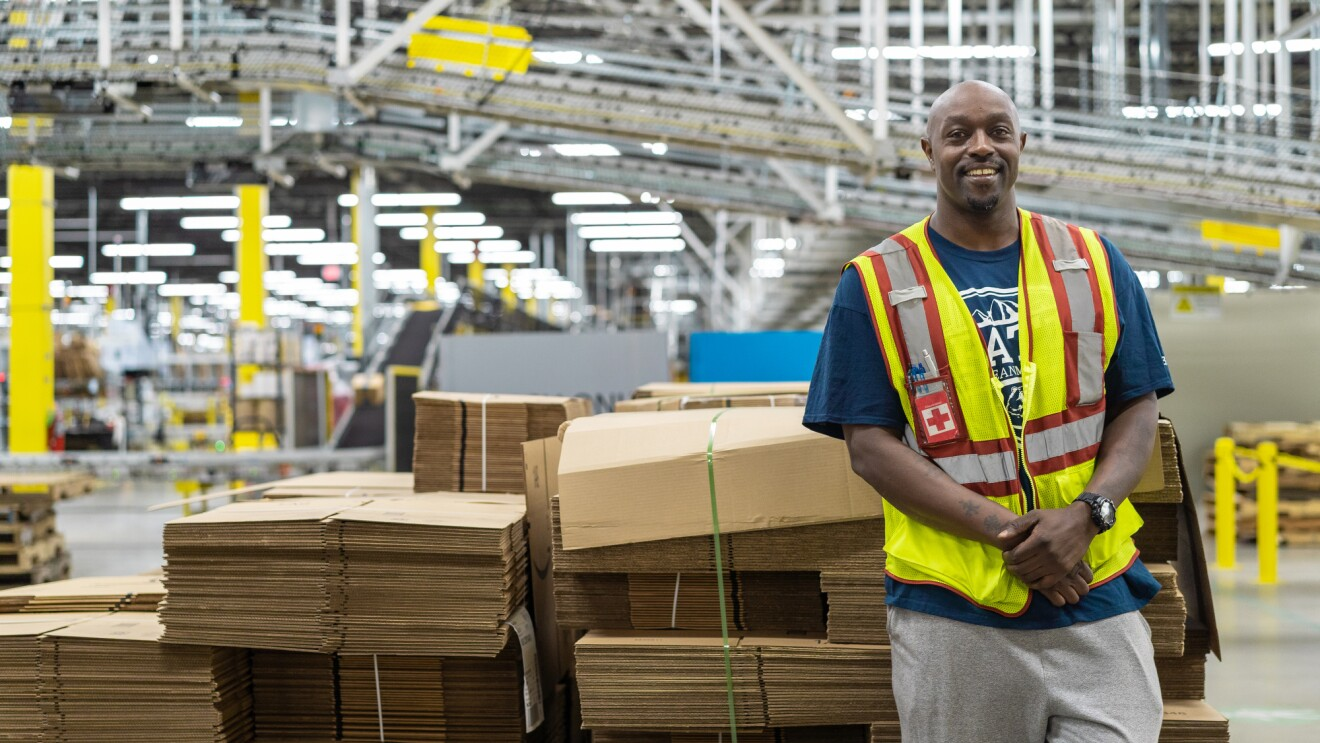 An Amazon employee works inside an Amazon fulfillment center, facing the camera.