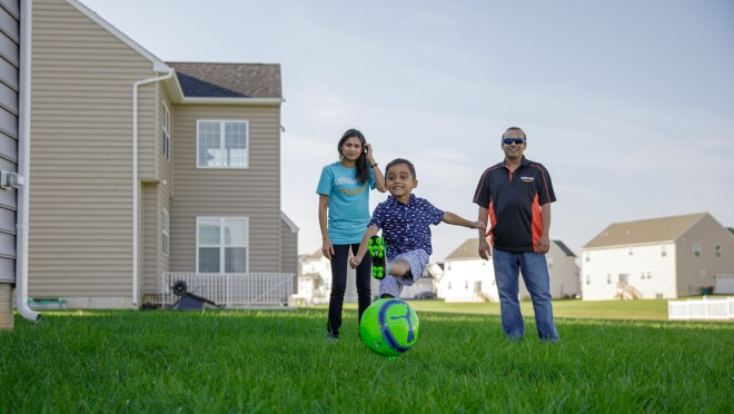 A young boy kicks a soccer ball on a lawn. He is flanked by a woman and a man, who watch as he plays.