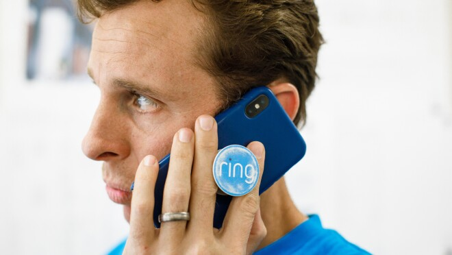 Jamie Siminoff, founder of Ring, in a blue t-shirt talks on a smartphone with a blue case. It has a Pop Socket that says Ring.