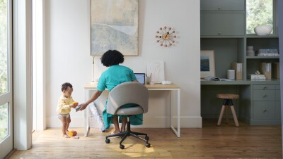 A woman sits at a desk, helping her toddler. On her desk is an Eero device.
